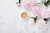 Morning coffee and beautiful pink peony flowers in flat lay style. Cozy breakfast on Mother or Woman day.