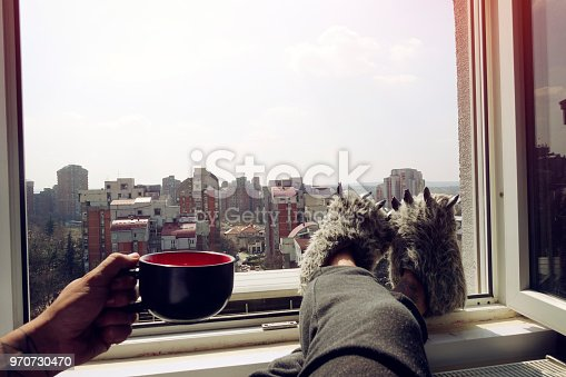 Man sitting by the window with feet up and holding cup of coffee