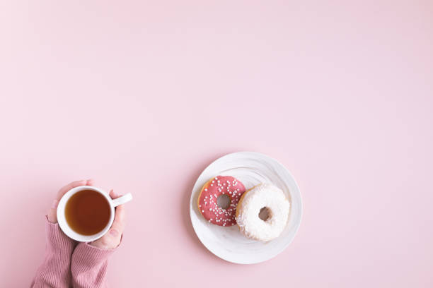 Morning coffee cup and sweet donut on pink pastel table, top view. Flat lay of cozy breakfast Morning coffee cup and sweet donut on pink pastel table, top view. Flat lay of cozy breakfast decorating a cake stock pictures, royalty-free photos & images