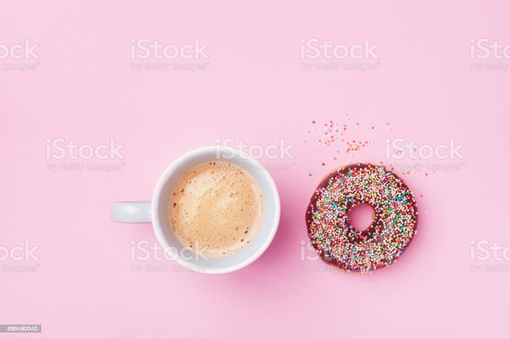Morning coffee cup and sweet pastry of chocolate donut on pink pastel table top view. Flat lay. Minimalism.