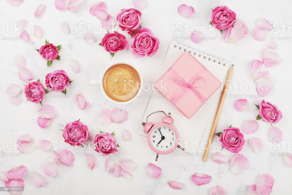 morning coffee cup gift box alarm clock and pink rose flowers on