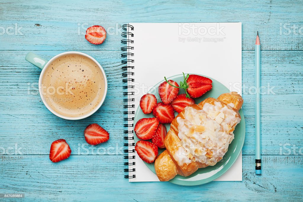Morning coffee cup with croissant, strawberry and notebook, flat lay
