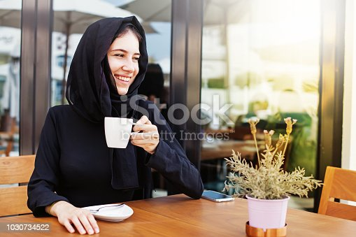 Beautiful arab woman in hijab and burka drinking coffee in cafe