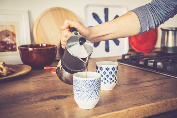 Morning coffee for two Time for coffee, woman Cooking morning coffee for two at home. coffee pot stock pictures, royalty-free photos & images
