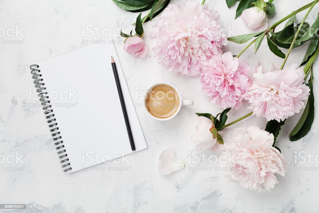 Morning coffee mug for breakfast, empty notebook, pencil and pink peony flowers. Flat lay. Woman working desk.