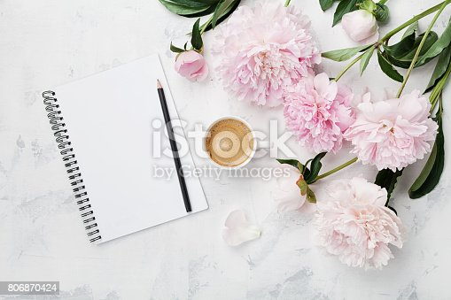 istock Morning coffee mug for breakfast, empty notebook, pencil and pink peony flowers. Flat lay. Woman working desk. 806870424