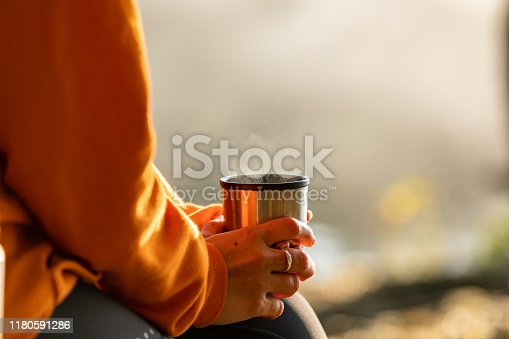 A woman wearing sports clothes is sitting on a bench outdoors holding a cup of coffee. The image is a close-up of her hands holding the cup.