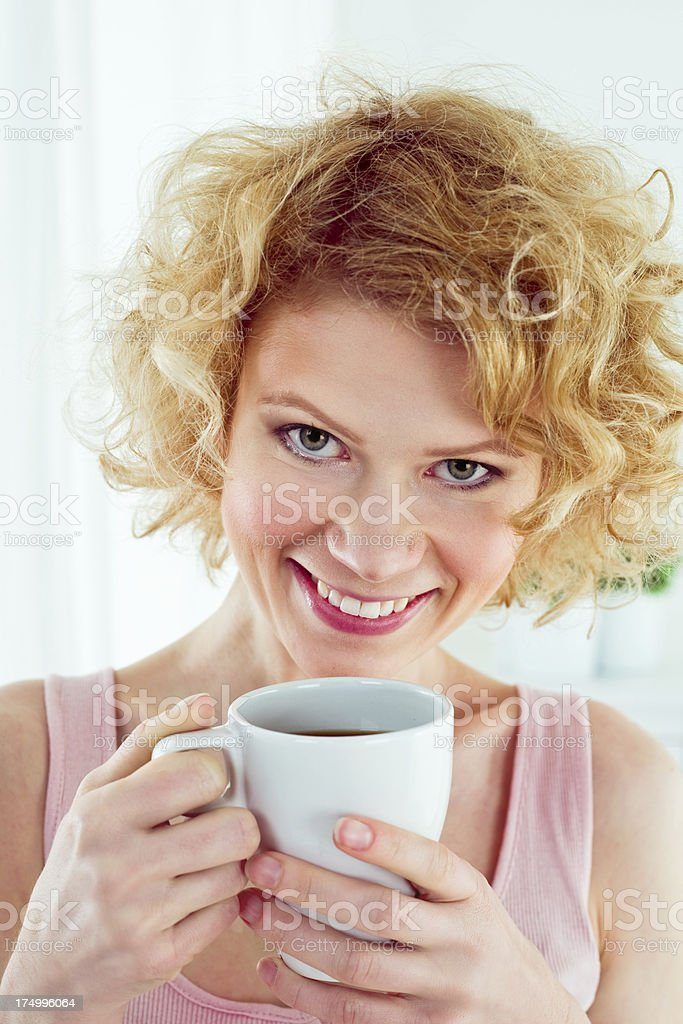 Morning coffee Happy young woman holding cup of coffee and smiling at the camera. 25-29 Years Stock Photo