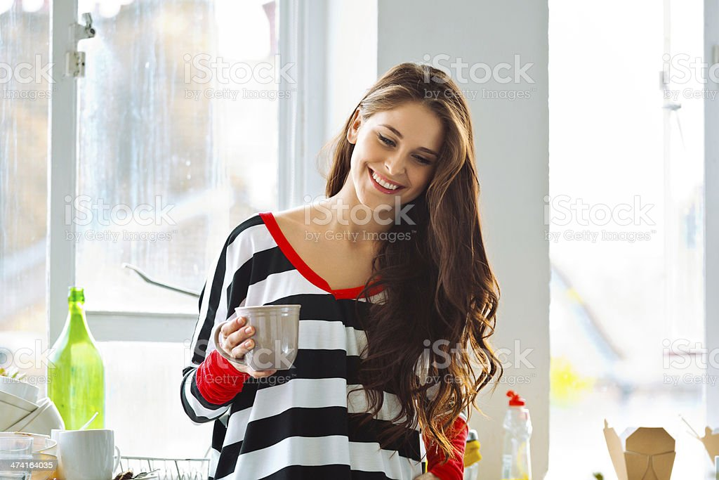 Morning coffee Smiling beautiful young woman standing in the kitchen with a cup of coffee. 20-24 Years Stock Photo