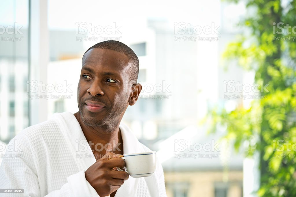 Morning coffee Afro american man wearing white bathrobe standing in her apartment with a cup of coffee in the morning. 30-39 Years Stock Photo