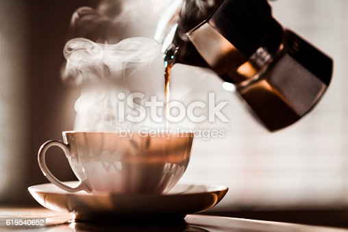 Coffee being poured into a coffee cup from Espresso Maker with beautiful steam in the morning light.