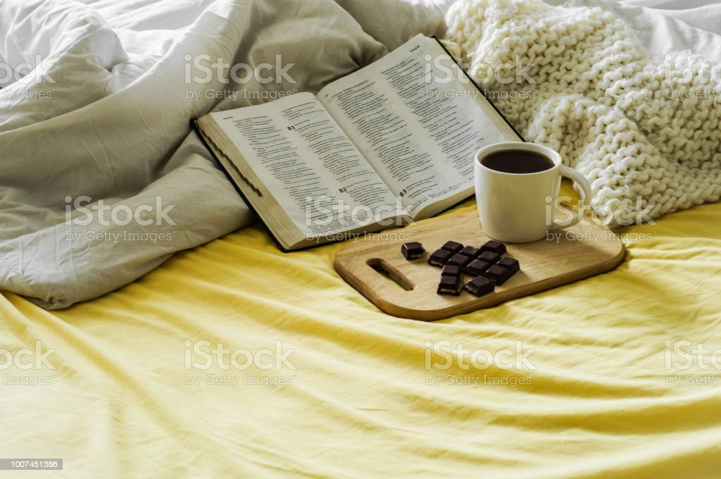 Morning Coffee With Bible Illuminated By Sunlight. Cup of coffee with Christian Bible. White bedroom. Chocolate and coffee cup. stock photo