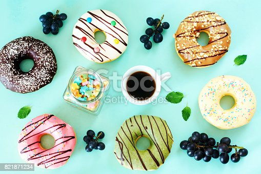 Assorted donuts (pistachio, caramel, strawberry, chocolate, vanila), grapes and cup of black coffee.