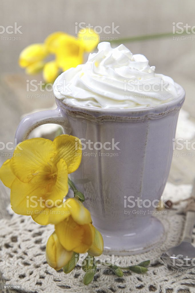 morning coffee with whipped cream, and fresia yellow flowers royalty-free stock photo