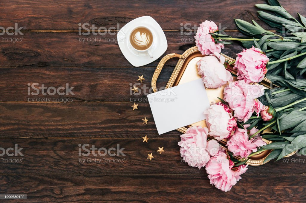 Morning concept. Coffee cup with pink peony on gold tray. Wedding, mothers day, valentines day