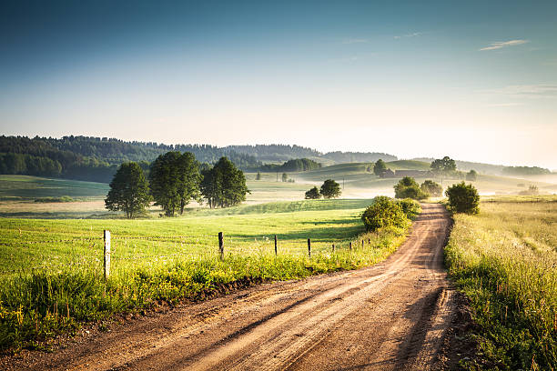 Morning Country Road through the Foggy Landscape - Colorful Countryside stock photo