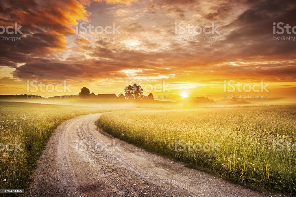 Morning Country Road through the Foggy Landscape - Colorful Sunrise royalty-free stock photo