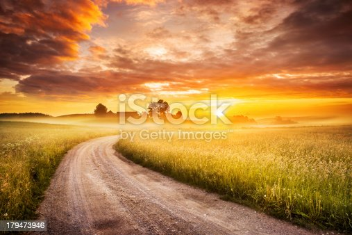 istock Morning Country Road through the Foggy Landscape - Colorful Sunrise 179473946