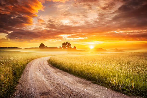 Morning Country Road through the Foggy Landscape - Colorful Sunrise stock photo