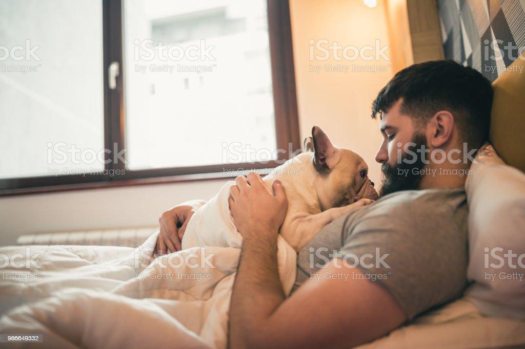 Morning cuddling, waking up with his dog stock photo