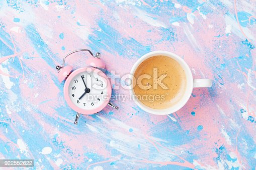 istock Morning cup of coffee and alarm clock on colorful working desk top view. Punchy pastel background. 922552622