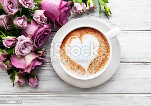 Morning cup of coffee and beautiful rose flowers on a light background, top view. Cozy breakfast. Flat lay