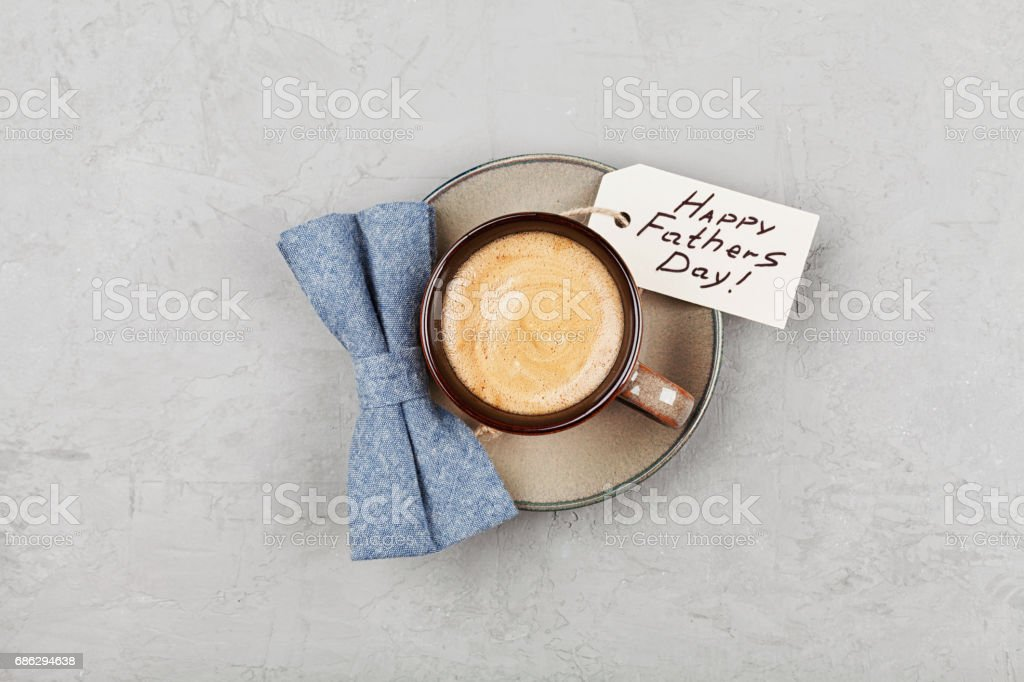 Morning cup of coffee and bowtie for breakfast on Happy Fathers Day. Flat lay. stock photo