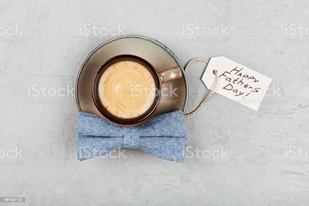 Morning cup of coffee and bowtie on stone table top view in flat lay style. Fathers Day concept. stock photo