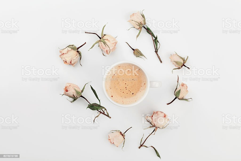 Morning Cup of coffee and dry roses flowers on white table from...