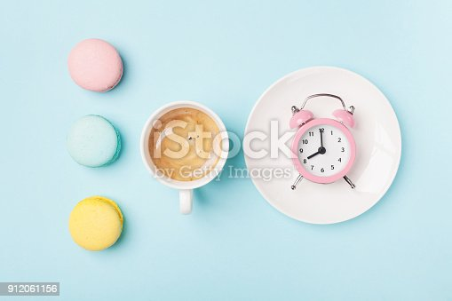 istock Morning cup of coffee, cake macaron and alarm clock on light turquoise table top view. Flat lay style. Sweet macaroons. 912061156