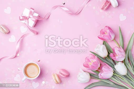 istock Morning cup of coffee, cake macaron, gift or present box and spring tulip flowers on pink background. Beautiful breakfast for Women day, Mother day. Flat lay. 1132050636
