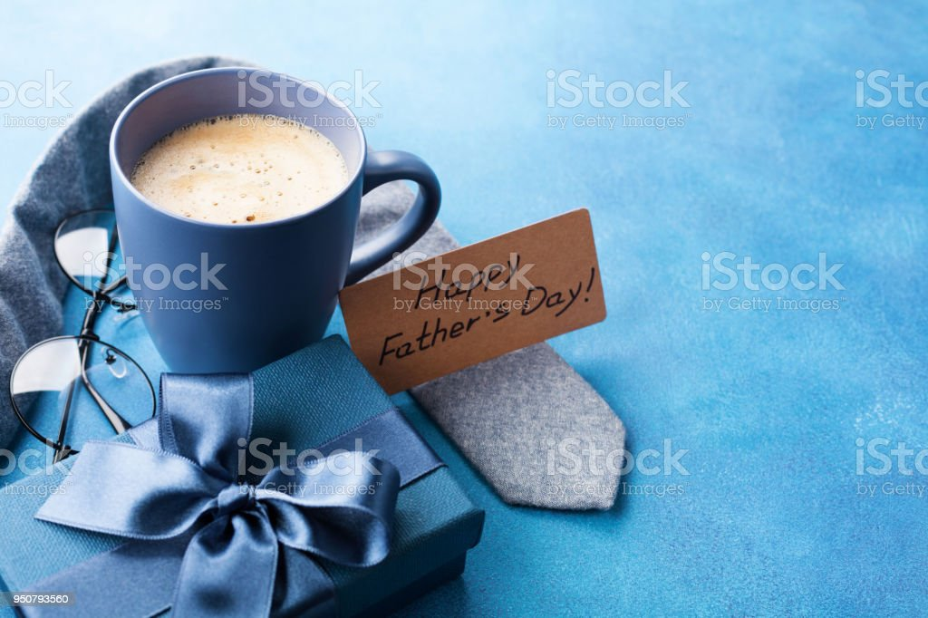 Morning cup of coffee, gift box, necktie and eyeglasses for greeting card on Happy Fathers Day. stock photo