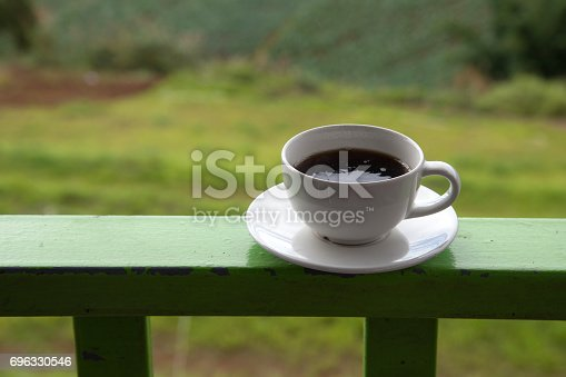 1135319558 istock photo Morning cup of coffee on green cabbage field background 696330546