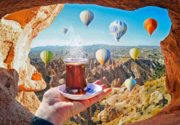 Morning cup of tea with view of colorful hot air balloons flying stock photo