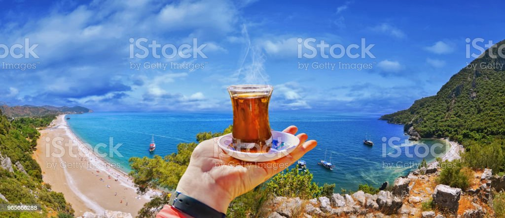 Morning cup of tea with view of colorful panoramic Olympos beach stock photo