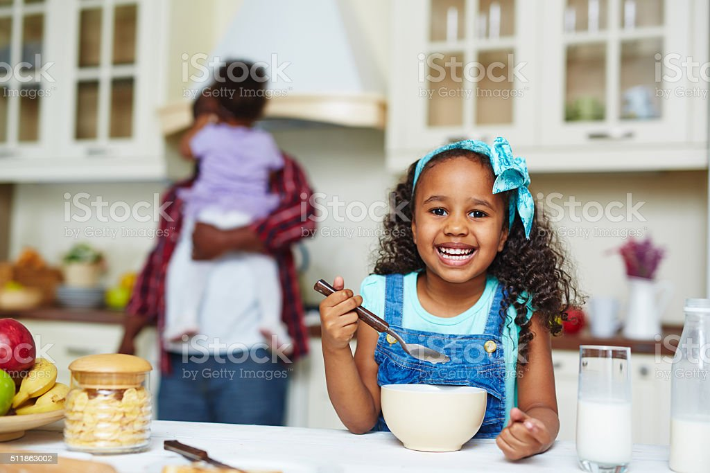 Morning eat Happy African-American girl eating morning cornflakes Adult Stock Photo