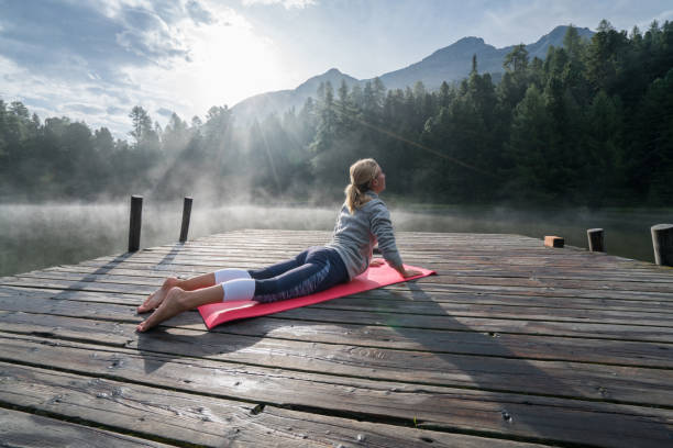 Morning exercising, woman waking up with Cobra pose yoga One young woman exercising yoga on a lake pier in the morning, fog on water surface. People wellbeing relaxation healthy lifestyle concept. cobra pose stock pictures, royalty-free photos & images