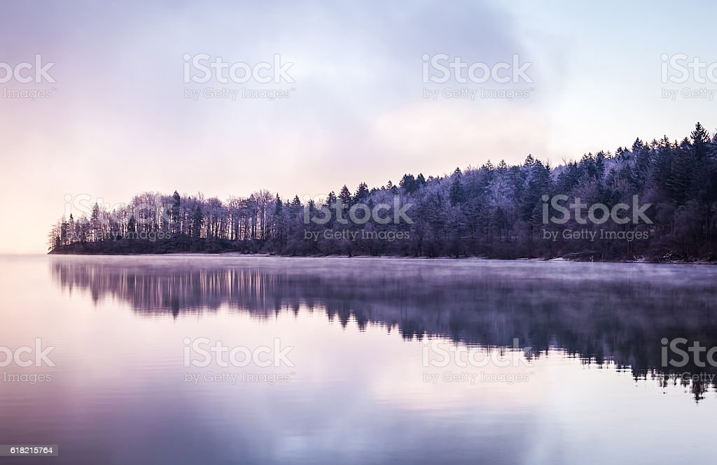 Morning fog and reflections on the lake. stock photo