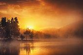 Morning fog on the lake, golden sunrise over the water.