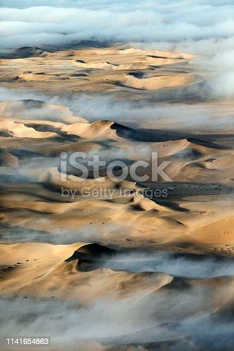 Morning fog over the great sand sea of Namibia near Sossusvlei, Sesrium, Namibia.