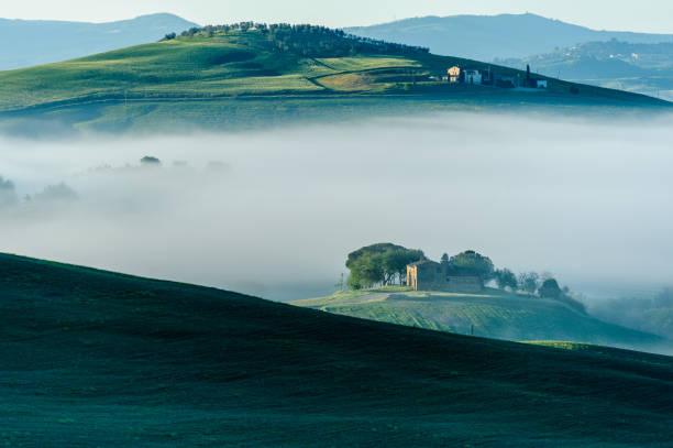Morning fog settles around farm stock photo