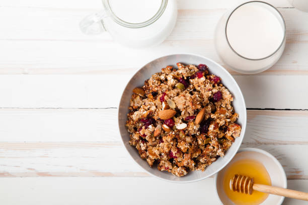 morning granola with dried fruits, honey, milk and berries on white wooden background. top view with copy space - muesli imagens e fotografias de stock
