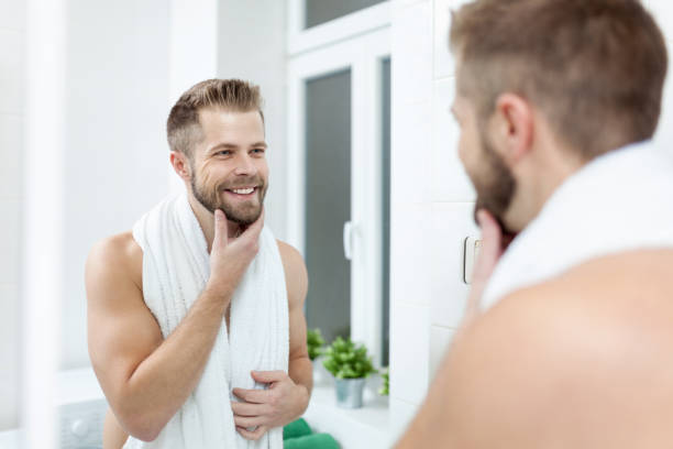 morning hygiene, man in the bathroom looking in mirror - beard stock pictures, royalty-free photos & images