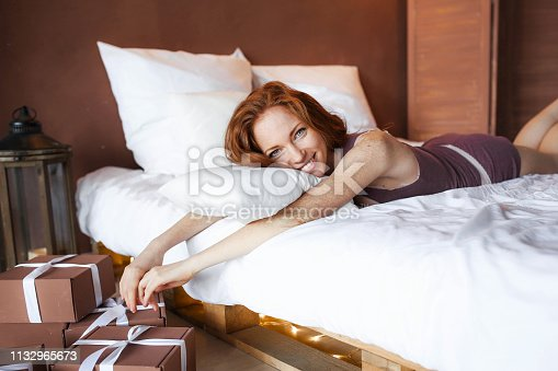 509031214istockphoto Morning in bed, a young charming red-haired woman with freckles lying in bed, hugging pillow, smiling, enjoying the morning 1132965673
