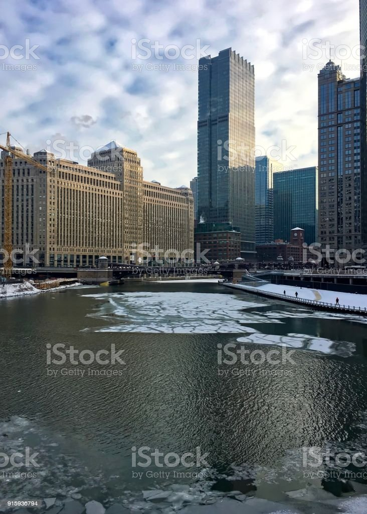 Morning in Chicago with interesting cloudscape over frozen Chicago River in winter. stock photo
