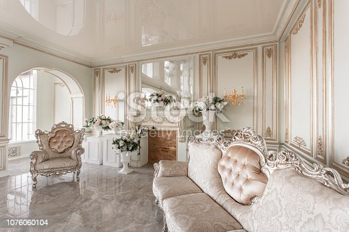 Morning in luxurious light interior in hotel. Bright and clean interior design of a luxury living room with stone floors, fireplace, sofa and chair . Stucco on walls.