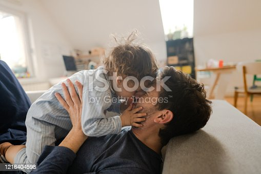 Photo of dad and little boy cuddling on the bed in the morning