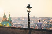 Young man sitting on the wall and watching city skyline during sunrise. Prague, Czech Republic