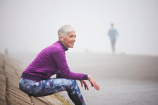 Morning jogging Beautiful mature woman jogging through fog in early autumn day only mature women stock pictures, royalty-free photos & images