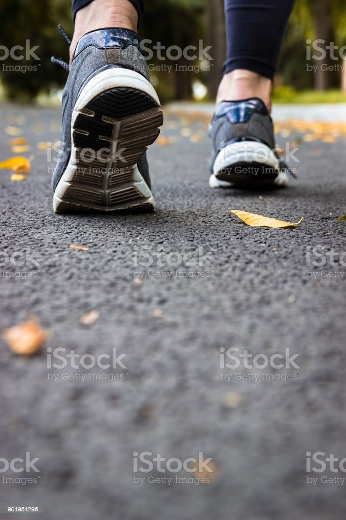 Morning jogging young woman outdoors. Sport shoes. Cardio workout. stock photo
